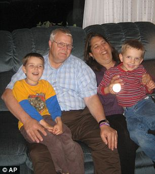 Happier times: Chuck and Judy Cox smile for a picture oh a green sofa with their grandsons, Charlie, left, and Braden, right