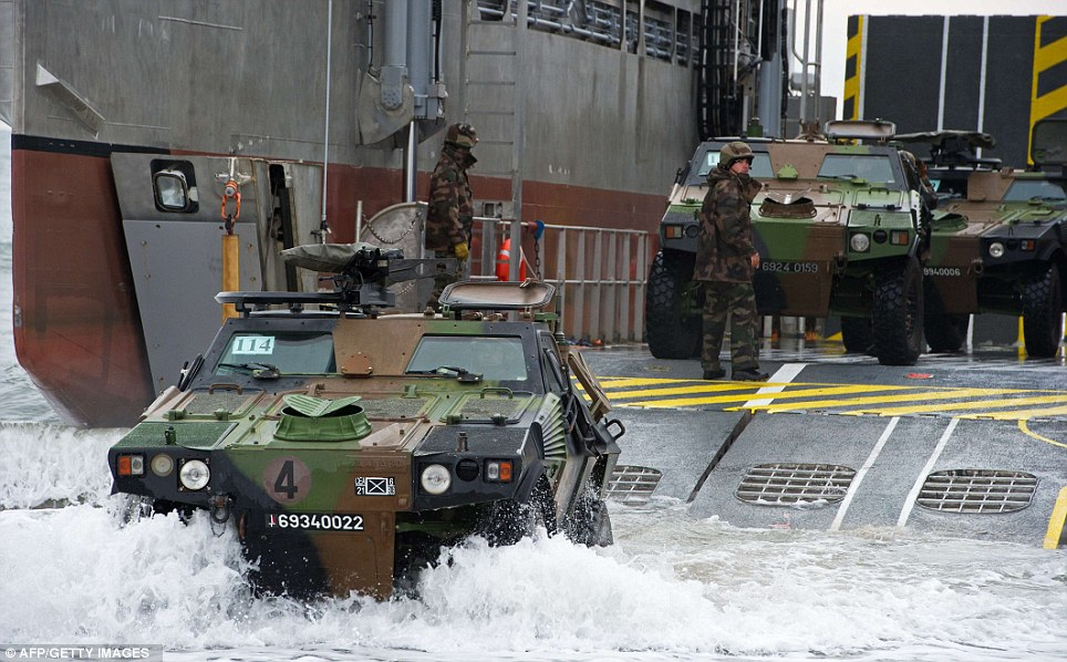 Cooperation: French vehicles and troops land from a LCAT transport catamaran as the operation gets underway
