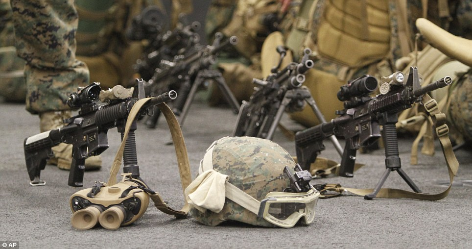 Equipment: Weapons, helmets and binoculars sit on the deck as Marines prepare to disembark