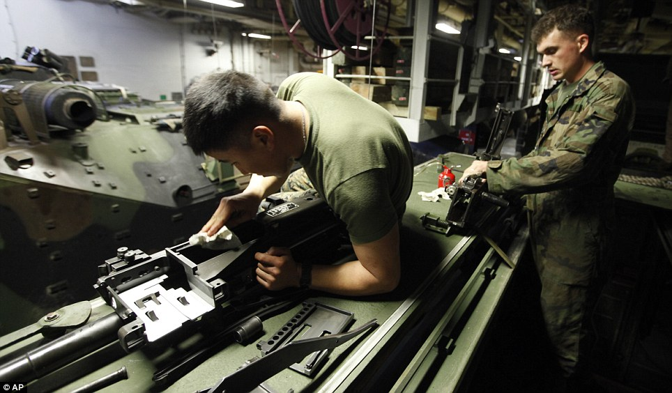 Duties: Two soldiers clean weapons on their AAVP7 assault vehicle on board the USS Wasp
