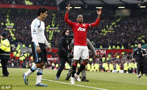 Joy unconfined: Evra celebrated wildly in front of Suarez at the final whistle