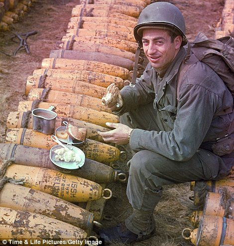 American soldier eating his dinner atop ammunition stockpiled for the impending D-Day invasion of France