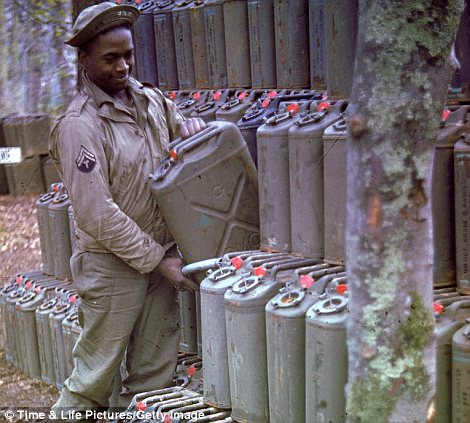 African American soldier piling up gas cans in preparation for the upcoming D-Day invasion of France
