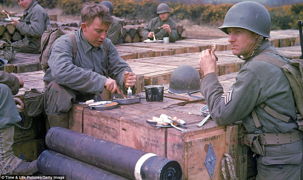 Dining out: American troops eat a meal set on top of boxes of ammunition amid preparation for the D-Day invasion of France