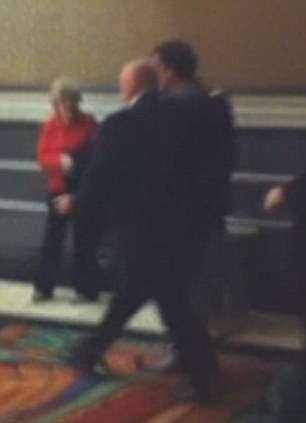 The senator is escorted out of the casino building