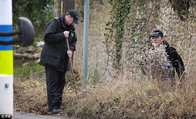 Police search the roadside near the vicarage where Mr Suddards was apparently killed