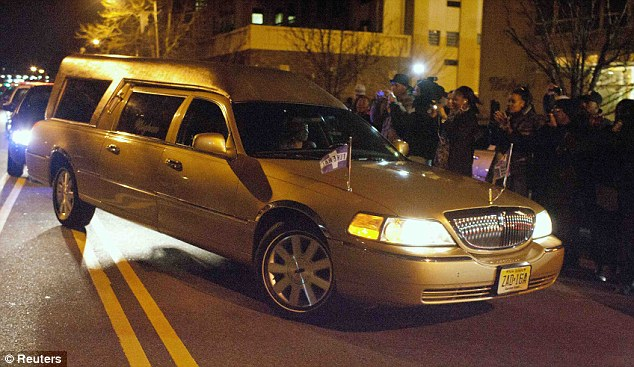 Home coming: The gold hearse carrying Whitney's body arrives at the funeral home in New Jersey on Monday night