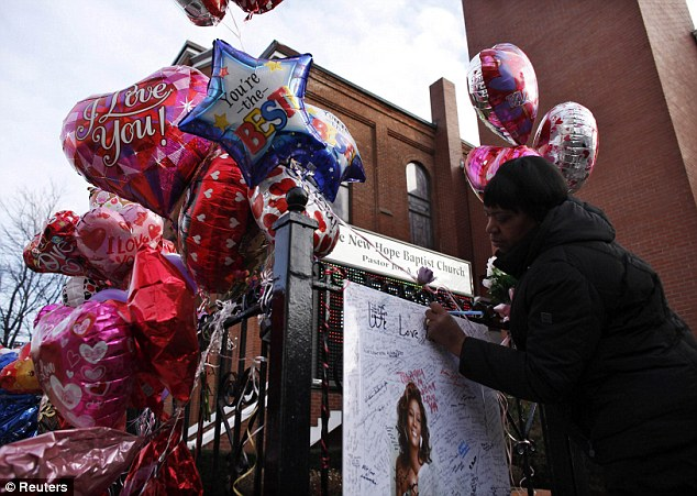 More love: A woman writes a message on a memorial for the pop singer