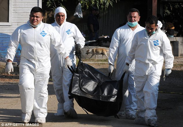 Clean up: The charred bodies of dead prisoners are continuing to be hauled out by forensic investigators in Honduras today