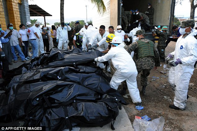 Removal: Honduran forensic workers and soldiers have had to take the bodies of hundreds of dead prisoners away