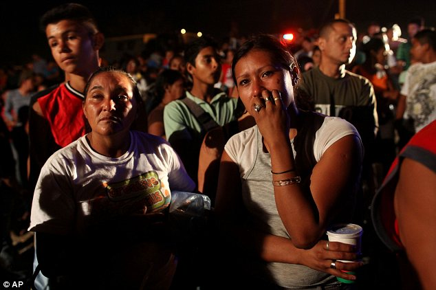 Mourning: Relatives of inmates stand outside the prison grieving for those who were killed in the blaze