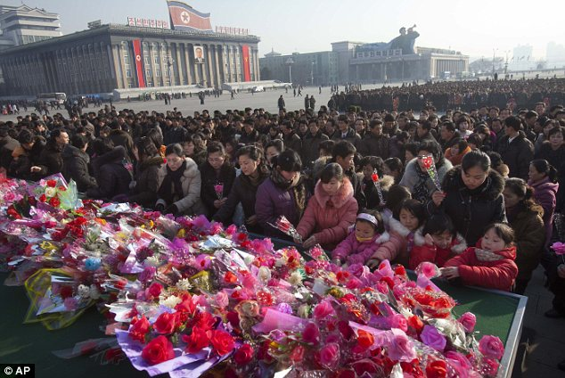 Tribute: North Koreans laid flowers at Kim Il Sung Square beneath a large portrait of the late leader Kim Jong Il today