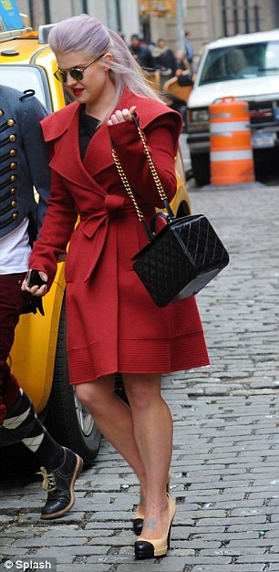 First look of the day: Kelly covered up in a red mac as she left her hotel before heading to the catwalk show