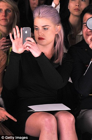 Taking notes: Kelly fitted in amongst the fashion elite in her LBD