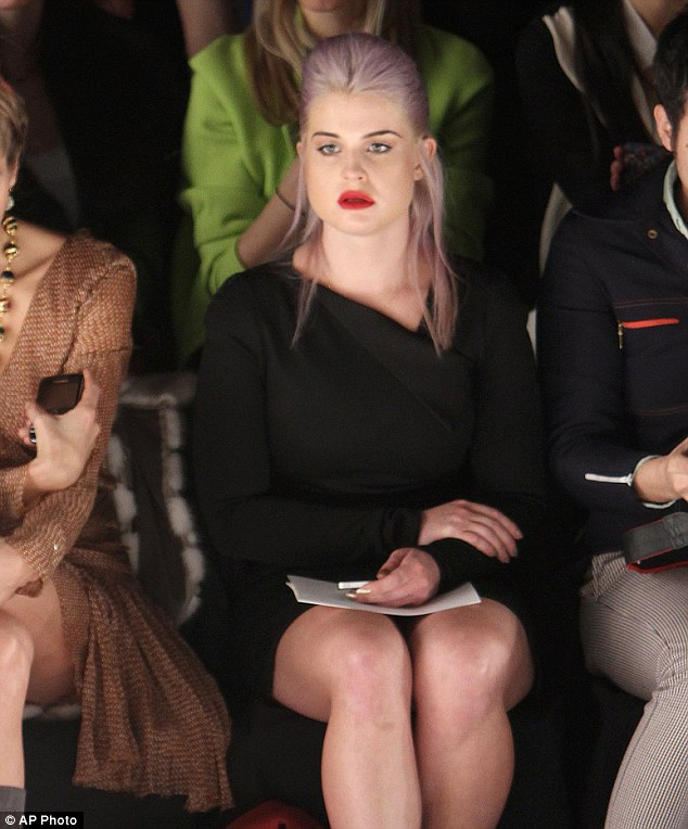 Serious: Kelly eyed up even more clothes on the front row at the show