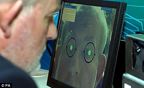 Then Home Secretary Charles Clarke sits at an iris scanner. The scheme cost £9million