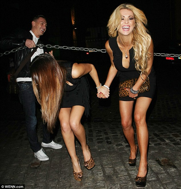 Swapping hands: Natasha locked fingers with Nicola McLean while Kirk held up a chain barrier for them