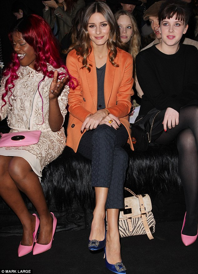 On the guest list: Olivia Palermo looked lovely in an orange jacket and animal print handbag