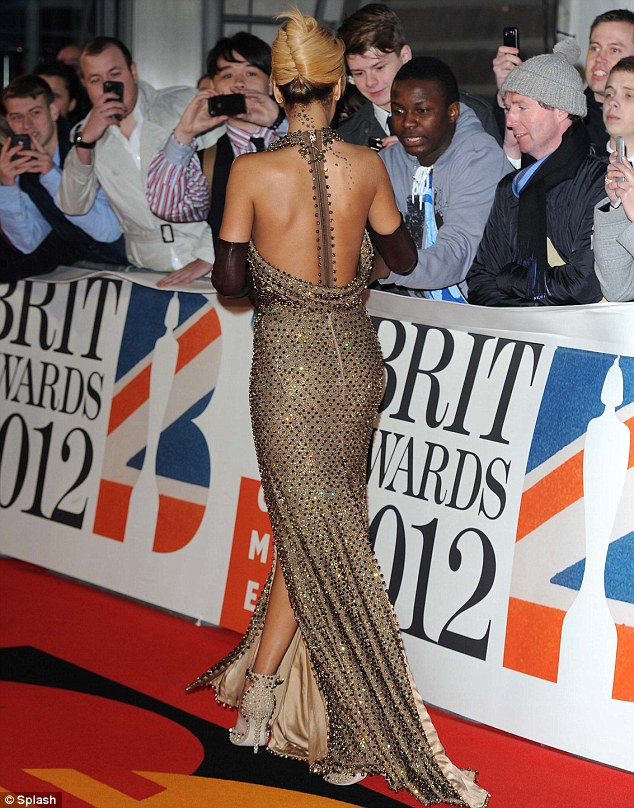 Glamour girl: Rihanna showed off the striking back of her dress as she signed autographs for fans