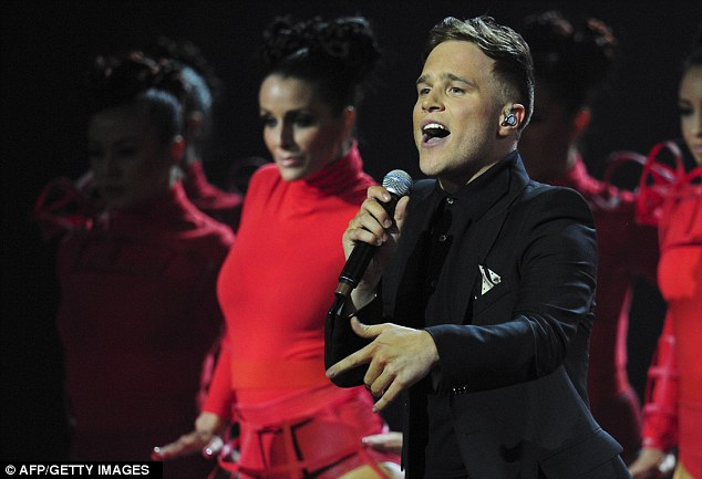 Lucky boy! British singer-songwriter Olly Murs performs with an array of scantily-clad dancers behind him