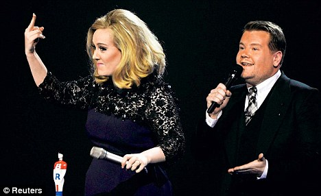 Hard done by: Adele gives the finger to 'the suits' after her acceptance speech was cut short at the Brit Awards