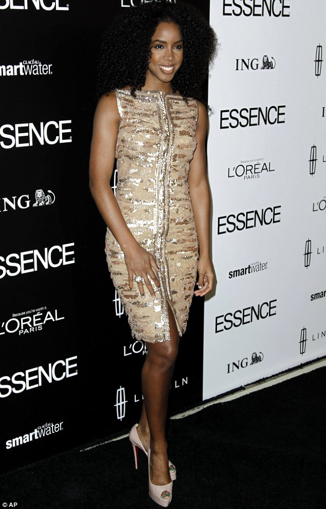Standing out from the crowd: Kelly Rowland shimmered in a silver and gold tiger print dress