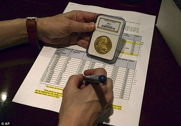 Keeping track: A member of Spain's Culture Ministry documents one of the coins from the sunken Nuestra Senora de las Mercedes