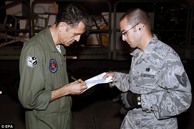 Read it and weep: A Spanish military commander signs a document that recognizes that Spain assumes the custody of the treasure trove before taking off to Spain from the McDill air base in Tampa, Florida