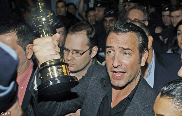 Don't drop it! The French actor looked proud to be holding the Best Actor award