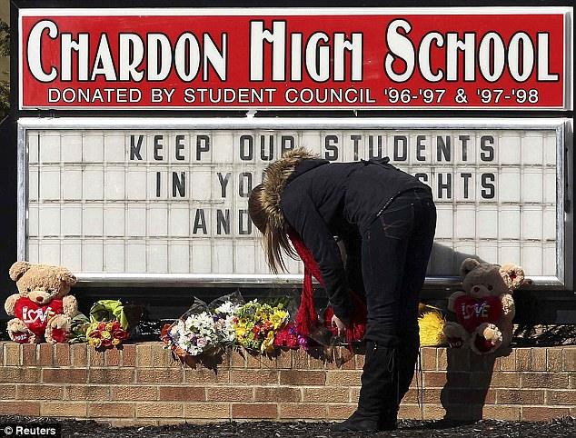 Sadness: A student places a bouquet of roses at the base of the Chardon High School sign on Monday