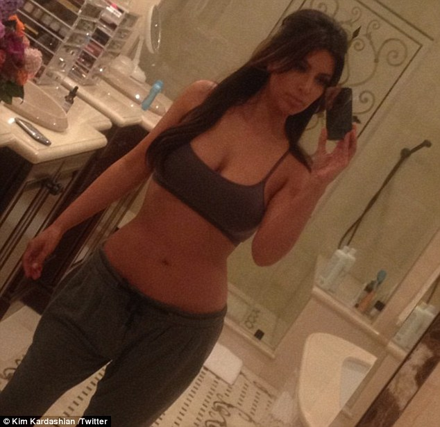Still as sexy as ever! Kim Kardashian shared a shot of herself with no make-up on, wearing a cropped sports top and loose jogging bottoms on her Twitter page