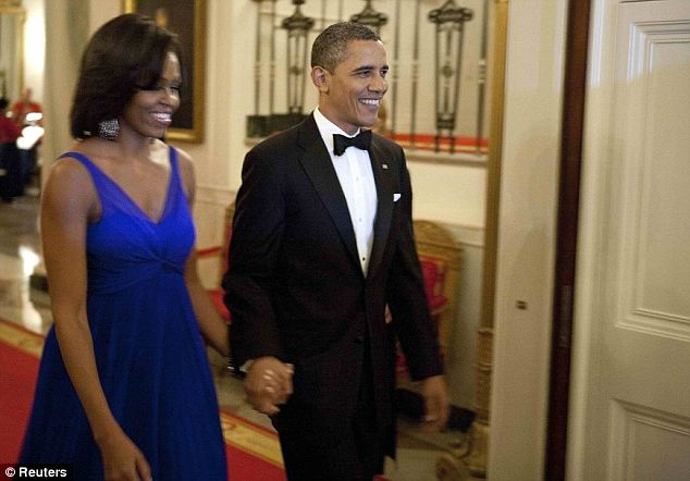 Happy together: The Obamas walked into the event all smiles and looking their best, with Mrs Obama wearing a beautiful blue gown with matching chandelier earrings