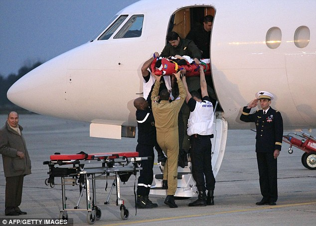 Home at last: Injured French journalist Edith Bouvier is carried out of a plane on a stretcher at the military airport of Villacoublay outside Paris today