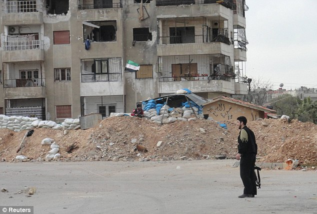 Last stand: A lone resistance fighter in the embattled neighbourhood of Baba Amr hours before government troops stormed the district yesterday