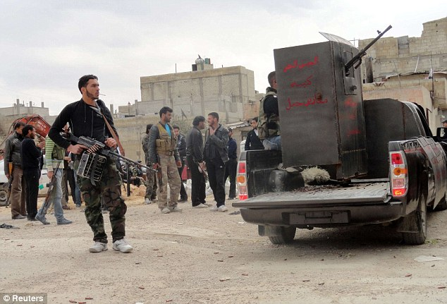 Readying themselves: Members of the Free Syrian Army deploy in Homs yesterday after the Syrian regime vowed to 'cleanse' the rebel-held district