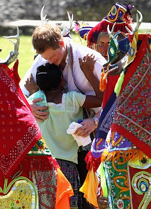 Feeling the love: The prince gets a hug from a girl amongst some performers dressed as deer
