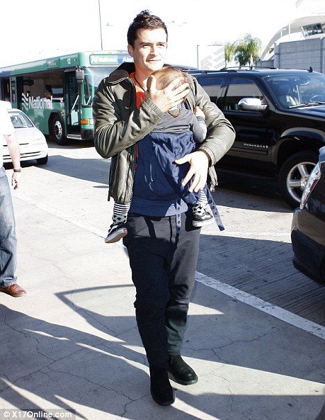 Fatherly duties: Orlando Bloom heads to LAX airport to catch a flight to Paris with his jetsetting baby son Flynn