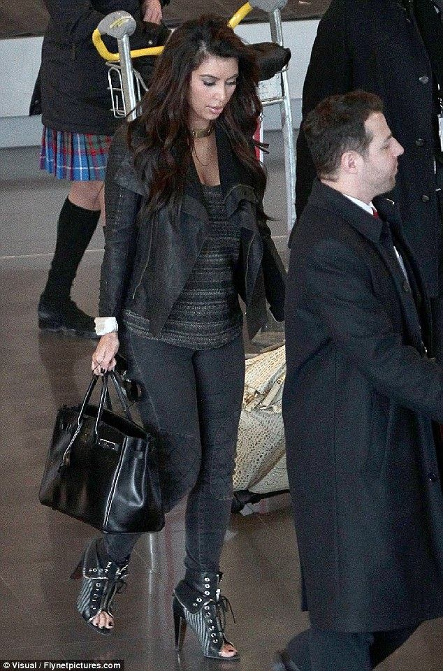 Biker chic: The single star slipped her voluptuous figure into a pair of washout black denim jeans, a knitted  sweater and a leather biker jacket