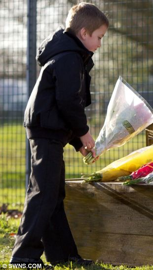 Showing support: A young boy lays flowers outside Battlesbury Barracks in Warminster