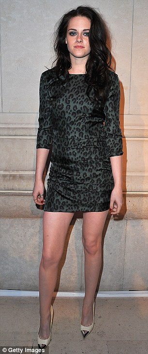 Hint of a smile: Kristen Stewart opted for a daringly short leopard print mini dress