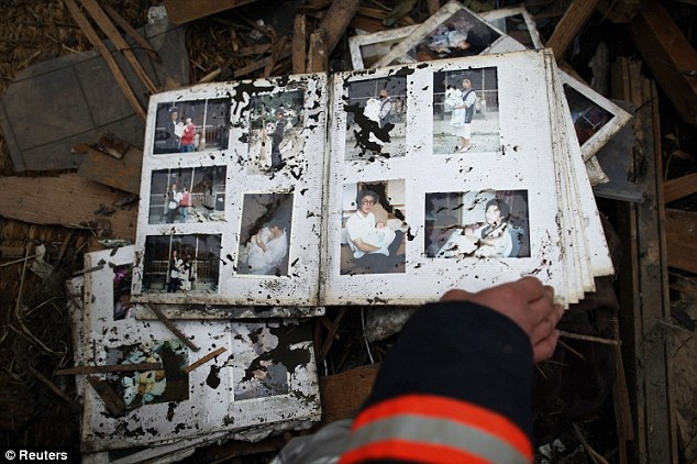 Haunting: A fireman goes through a photo album found in the ruins of the devastated town of Otsuchi