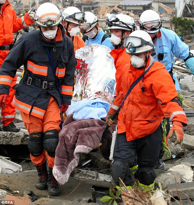 Survivor: Relief workers carry a man who survived being buried for five days in the remains in Ishimaki town