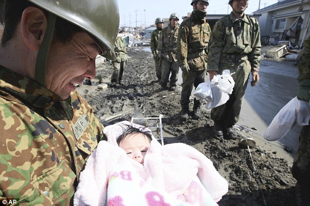 Emotion: A soldier breaks holds back the tears after rescuing a four-month-old baby girl in Ishinomaki, northern Japan, three days after the earthquake hit