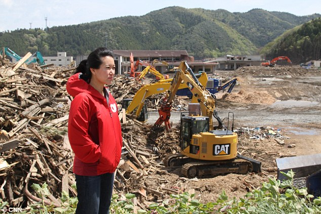 Devastation: Kyung Lah, CNN's Tokyo correspondent, surveys the aftermath of the Japanese tsunami which killed tens of thousands of people