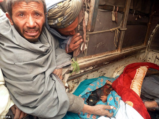 Disbelief: Two grief-stricken Afghan men look into the van where the body of a badly burned child is wrapped in a blue blanket following the shooting