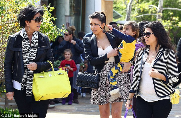 Family time: Kim assumed aunt duties as she strolled with sister Kourtney and mother Kris Jenner