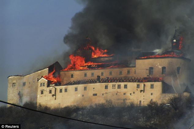 Up in smoke: A fire rips through the Krasna Horka castle, near Roznava, eastern Slovakia, after police suspect a discarded cigarette lit dry grass nearby