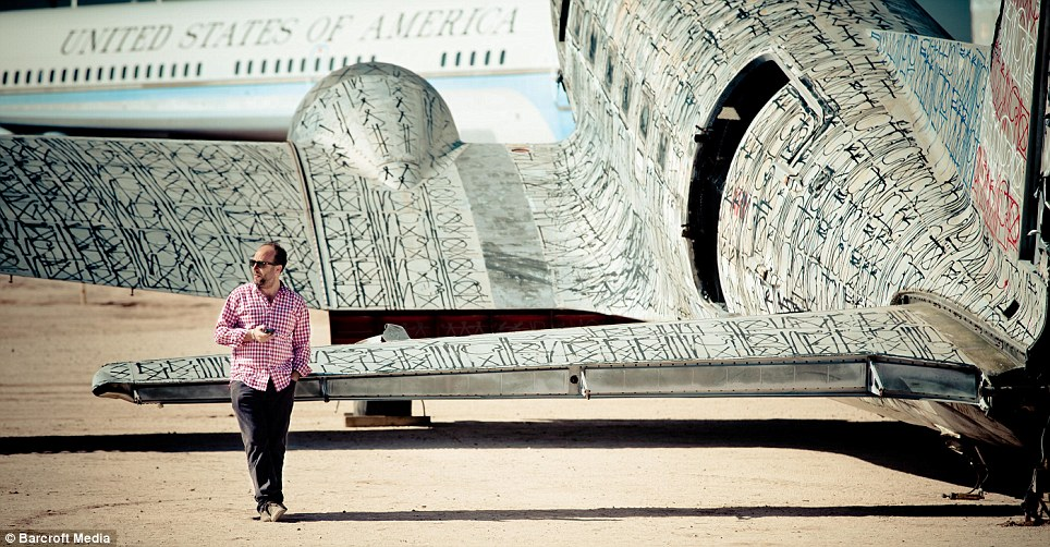 Job complete: Artist Retna leans against a graffiti-covered Douglas DC-3, called 'Warning Shot', which retains some elements of the United States flag