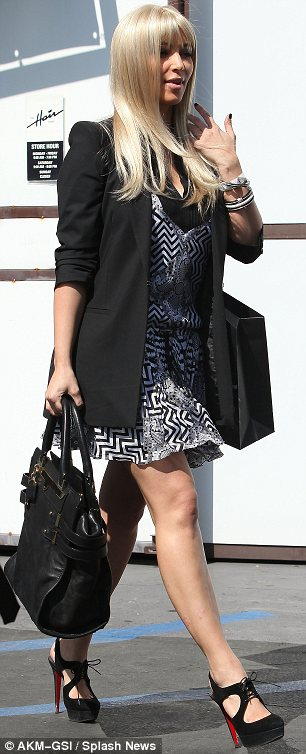 Completing her look: Kim teamed the blonde wig with a monochrome patterned dress, a black blazer and matching shoes