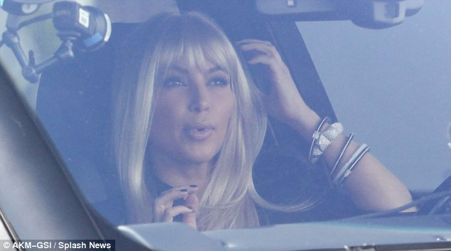 How do I look?: Kim pouted as she checked out her reflection in her rear view mirror